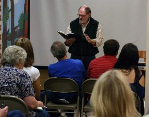 David Allan Evans speaks at a poetry reading.